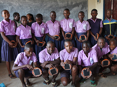 A class of students holding their Mwezi solar lights.