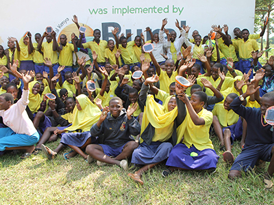 A class of students, holding their Mwezi solar lights in the air.