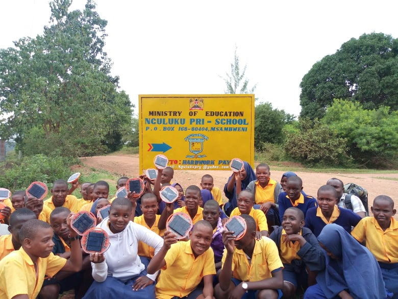 A group of students, waving their Mwezi solar lights in the air
