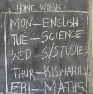 a chalkboard with a timetable of lessons written on it.