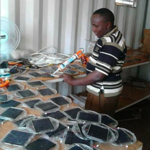 Our technical manager, John, making some Mwezi solar lights.