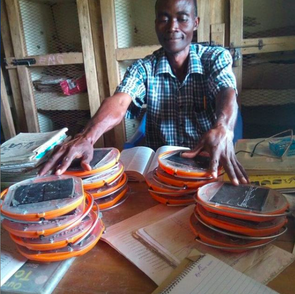 Mr Kennedy from Kikonde Primary School, receiving a light library from the Mwezi Foundation.