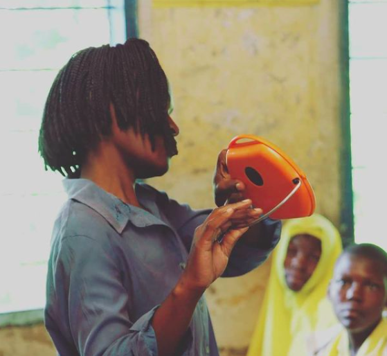 Julia, teaching a class of students how to use their Mwezi solar lights.