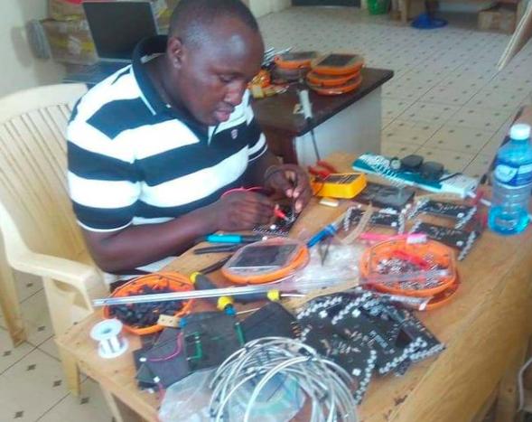 John, repairing some broken Mwezi solar lights.