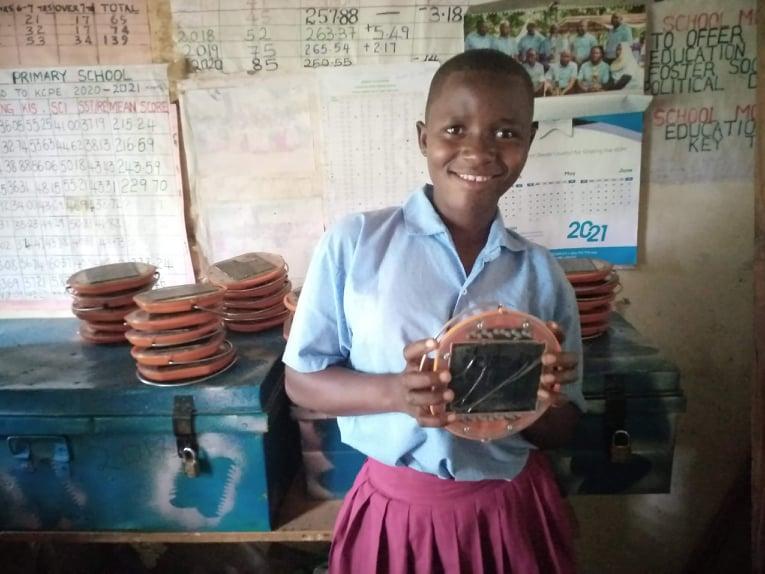 A student from Vitsangalaweni school, holding a Mwezi solar light