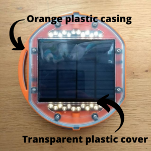 a Mwezi solar light with an orange plastic casing and a transparent plastic cover.